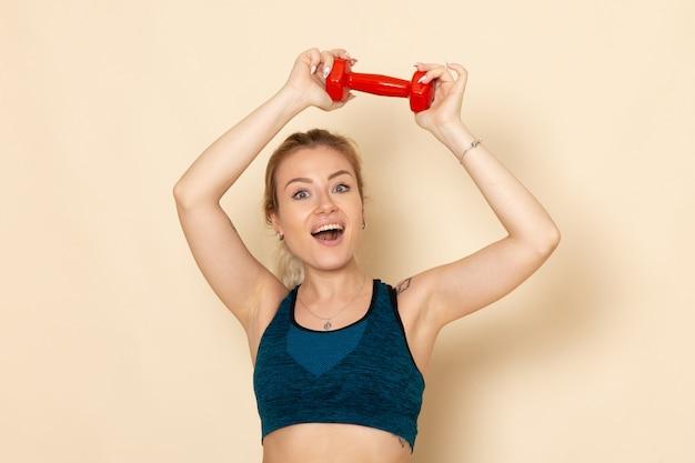 Giovane femmina di vista frontale in attrezzatura sportiva che tiene i dumbbells