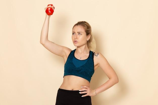 Giovane femmina di vista frontale in attrezzatura di sport che tiene i dumbbells rossi sulla donna di allenamento di bellezza di salute del corpo di sport della parete bianca
