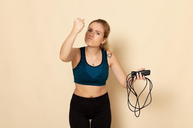 Giovane femmina di vista frontale in attrezzatura di sport che tiene le corde di salto e che si sente arrabbiato sugli esercizi di bellezza di sport del corpo di allenamento di salute della parete bianca