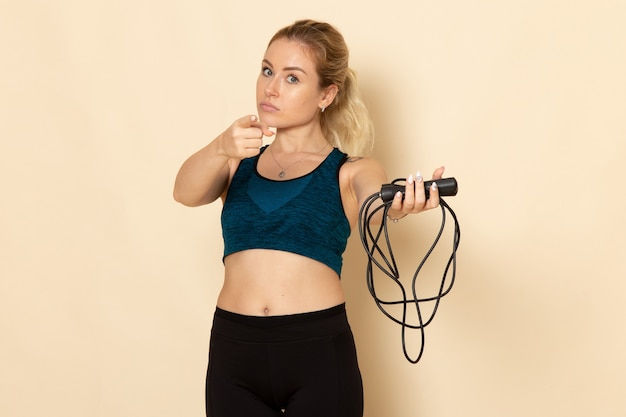 Front view young female in sport outfit holding skipping ropes on the light white wall health beauty workout body sport