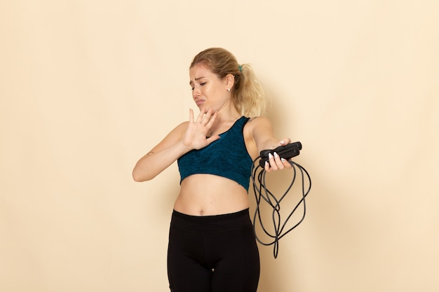 Front view young female in sport outfit holding skipping ropes on white desk health workout body sport beauty exercises