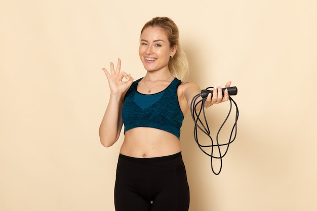 Front view young female in sport outfit holding skipping ropes on the white wall health beauty workout body sport