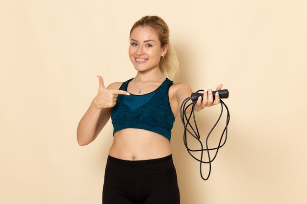 Front view young female in sport outfit holding skipping ropes on white wall health beauty workouts jump body sport