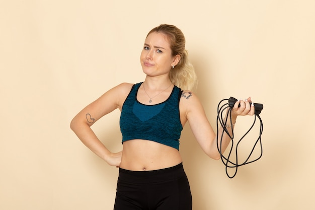 Front view young female in sport outfit holding skipping ropes on white wall health workout body sport beauty exercise