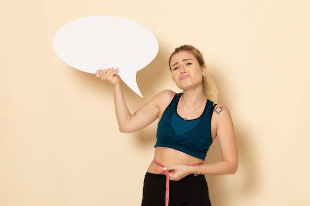 Giovane femmina di vista frontale in attrezzatura di sport che tiene segno bianco