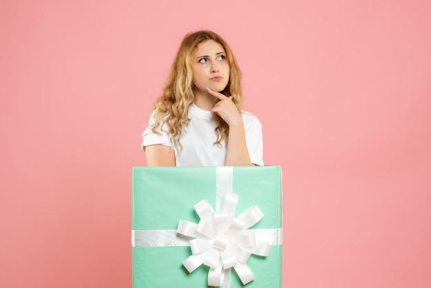 青いプレゼントボックスの中に立っている正面図若い女性