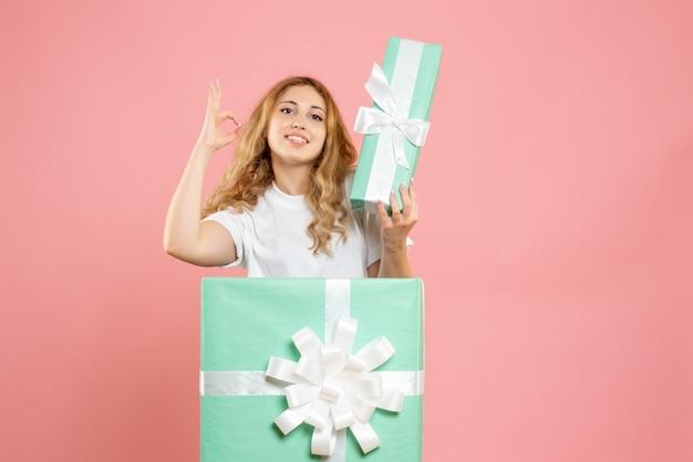 プレゼントを保持しているボックスの中に立っている正面図若い女性