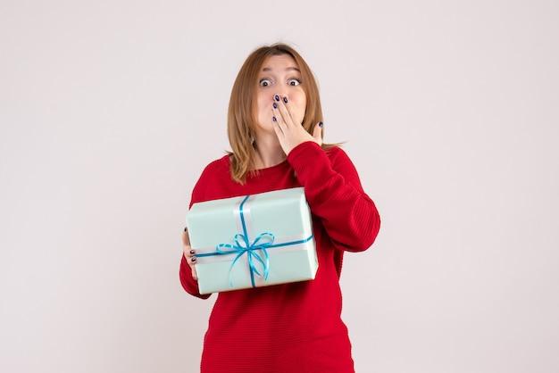 Вид спереди молодая женщина, стоящая с подарком на рождество