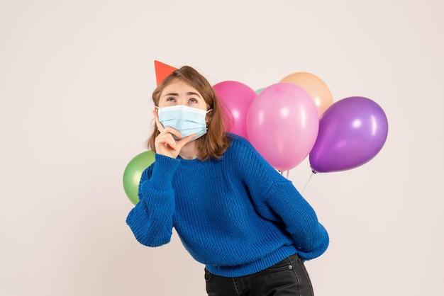 Vista frontale giovane femmina in maschera sterile che nasconde palloncini colorati dietro la schiena