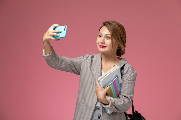 Vista frontale giovane studentessa in cappotto grigio in posa tenendo i libri prendendo un selfie sullo sfondo rosa lezioni di studio universitario