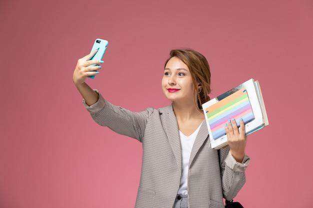 Vista frontale giovane studentessa in cappotto grigio in posa tenendo i libri con il sorriso prendendo un selfie sullo sfondo rosa lezioni di studio universitario