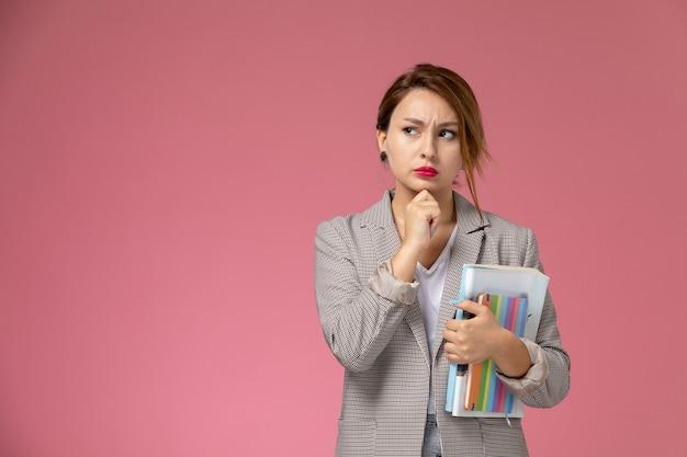 Vista frontale giovane studentessa in cappotto grigio in posa e in possesso di libri con espressione di pensiero sullo sfondo rosa lezioni di studio universitario