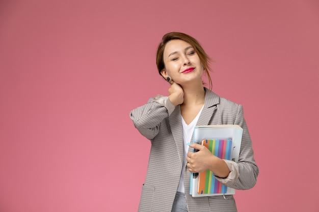 Vista frontale della giovane studentessa in cappotto grigio in posa tenendo il quaderno e avendo mal di collo sullo sfondo rosa lezioni di studio universitario