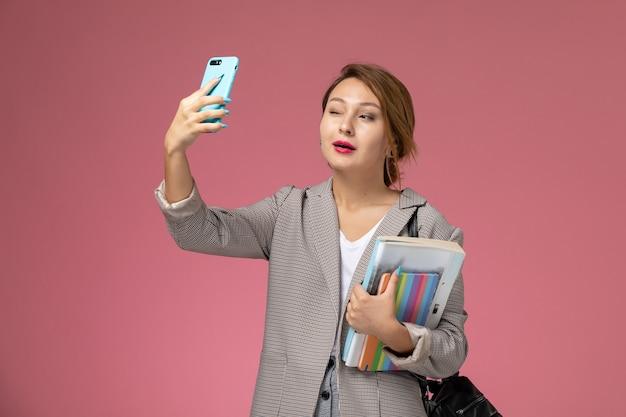 Vista frontale giovane studentessa in cappotto grigio in posa e prendendo un selfie su sfondo rosa lezioni di studio universitario