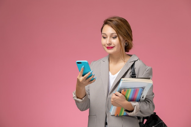 Front view young female student in grey coat posing and using phone on the pink background lessons university college study