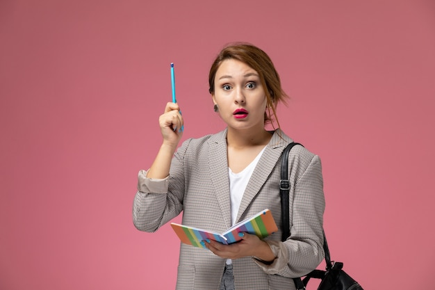 Front view young female student in grey coat posing with copybook remembered something on pink background lessons university college study