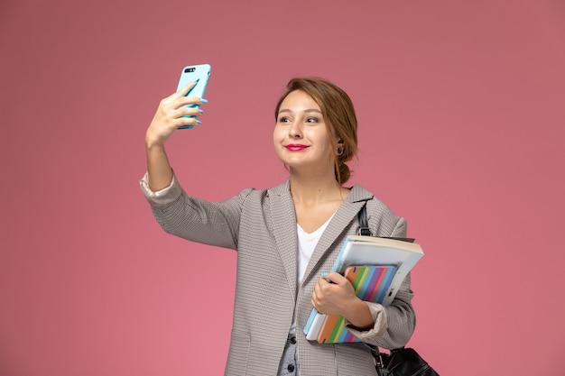 Vista frontale giovane studentessa in cappotto grigio in posa con quaderni e prendendo un selfie su sfondo rosa lezioni di studio universitario