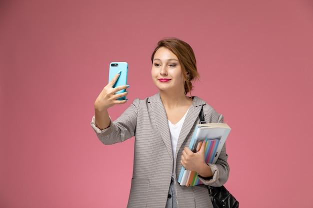 Vista frontale giovane studentessa in cappotto grigio con quaderni prendendo un selfie su sfondo rosa lezioni di studio universitario