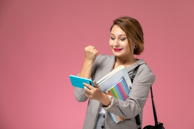 Front view young female student in grey coat with copybooks and using a phone with smile on the pink background lessons university college study