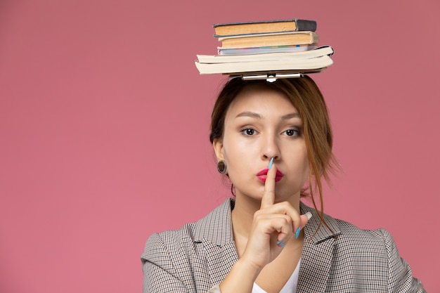 Front view young female student in grey coat with on her head showing silence sign on pink background lessons university college study