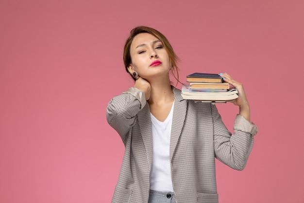 ピンクの背景のレッスン大学の大学の研究の本をポーズと保持している灰色のコートの若い女子学生の正面図