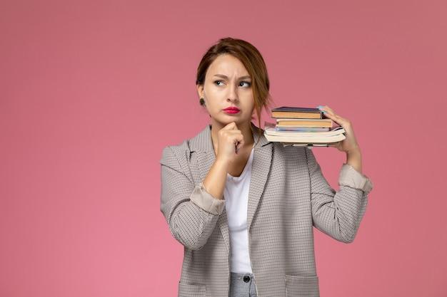 ピンクの背景のレッスン大学の大学の研究を考えてポーズをとって本を保持している灰色のコートの若い女子学生の正面図