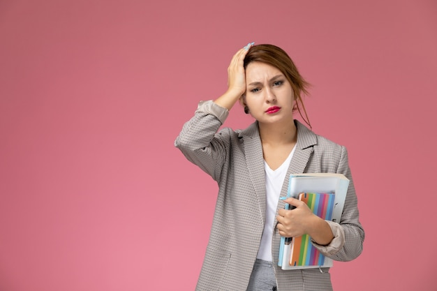 正面図ピンクの背景に頭痛の種を持って本を持ってポーズをとる灰色のコートの若い女子学生