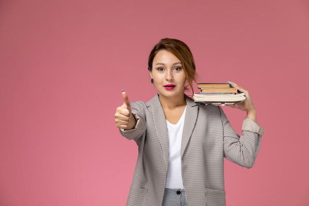 ピンクの背景のレッスン大学の大学の研究のサインのように表示されている本を持ってポーズをとって灰色のコートを着た若い女子学生の正面図