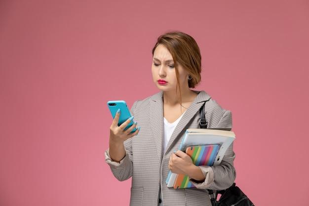 ピンクの背景のレッスン大学大学の研究で電話を使用して本を持ってポーズをとる灰色のコートの若い女子学生