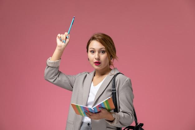 ピンクの背景のレッスン大学の大学の研究に上げられたペンでコピーブックを保持してポーズをとって灰色のコートの若い女子学生の正面図