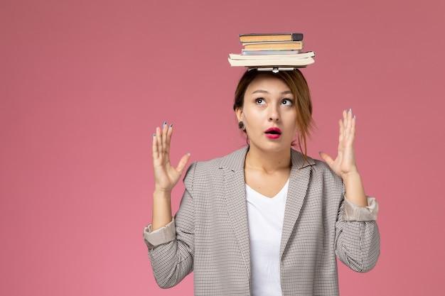 ピンクの背景のレッスン大学大学の研究書に彼女の頭の上の本でポーズをとって灰色のコートの若い女子学生の正面