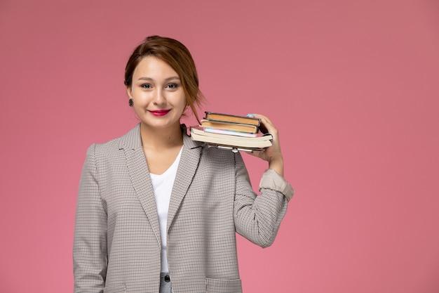 Вид спереди молодая студентка в сером пальто, улыбаясь, держит книги на розовом фоне, урок университетского колледжа, учебная книга