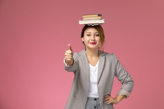 ピンクの背景のレッスンに笑みを浮かべて彼女の頭にコピーブックと灰色のコートを着た若い女子学生の正面図大学大学の研究