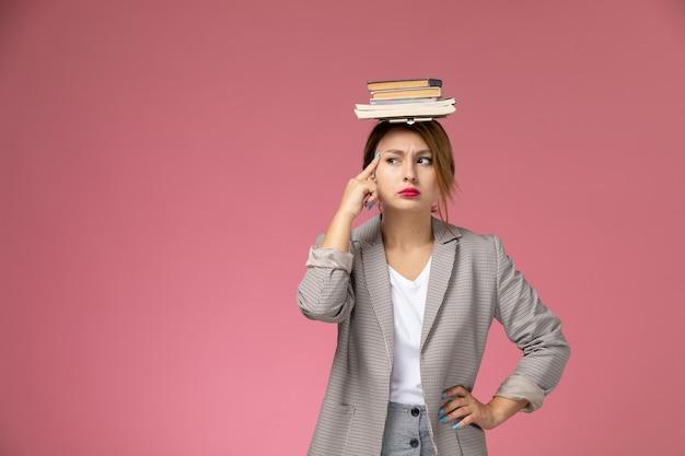 ピンクの背景のレッスンで思考表現と彼女の頭にコピーブックと灰色のコートを着た若い女子学生の正面図大学大学の研究
