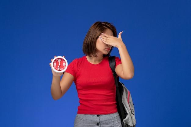水色の背景に時計を保持しているバックパックを身に着けている赤いシャツの正面図若い女子学生。