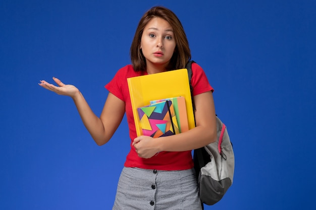 水色の背景にコピーブックとファイルを保持しているバックパックを身に着けている赤いシャツの正面図若い女子学生。