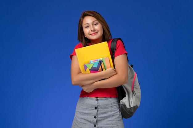Молодая студентка вид спереди в красной рубашке носить рюкзак, держа тетрадь и файлы на светло-синем фоне.