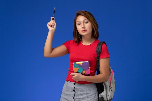 水色の背景にコピーブックを保持しているバックパックを身に着けている赤いシャツの正面図若い女子学生。