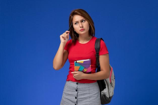 青い背景に考えているコピーブックを保持しているバックパックを身に着けている赤いシャツの正面図若い女子学生。