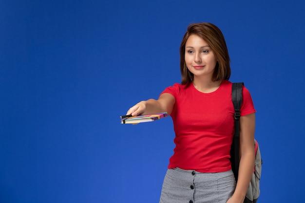 青い背景にペンでコピーブックを保持しているバックパックを身に着けている赤いシャツの正面図若い女子学生。