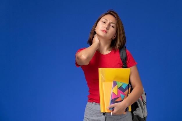 ファイルと青い背景に首の痛みを持っているコピーブックを保持しているバックパックを身に着けている赤いシャツを着た若い女子学生の正面図。
