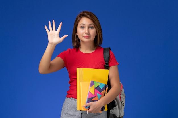 ファイルと青い背景に彼女の手のひらを示すコピーブックを保持しているバックパックを身に着けている赤いシャツを着た若い女子学生の正面図。