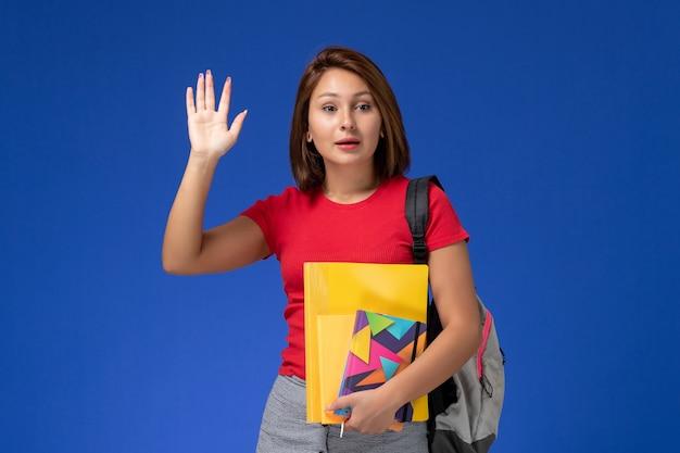 ファイルと青い背景に手を振っているコピーブックを保持しているバックパックを身に着けている赤いシャツの正面図若い女子学生。