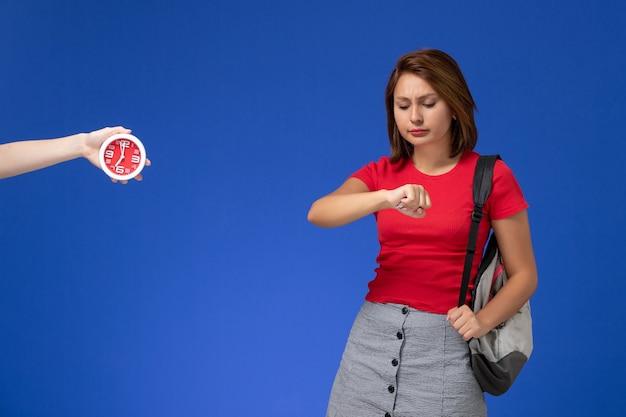 水色の背景に彼女の手首を見ているバックパックを身に着けている赤いシャツを着た若い女子学生の正面図。