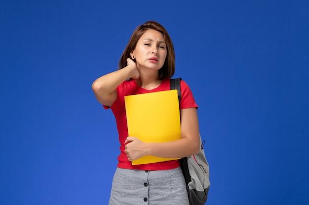 Вид спереди молодая студентка в красной рубашке с рюкзаком, держащим желтые файлы с шейной болью на голубом фоне.