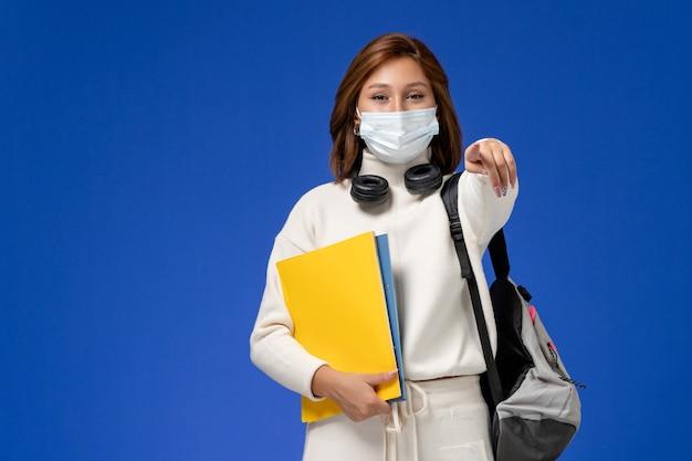 青い壁にファイルを保持しているマスクとバックパックを身に着けている白いジャージの正面図若い女子学生