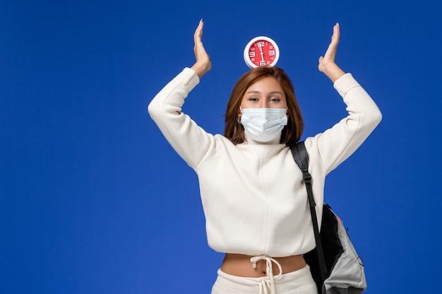 마스크를 착용하고 파란색 책상 수업 대학 대학 학교 책에 시계를 들고 흰색 저지에 전면보기 젊은 여성 학생