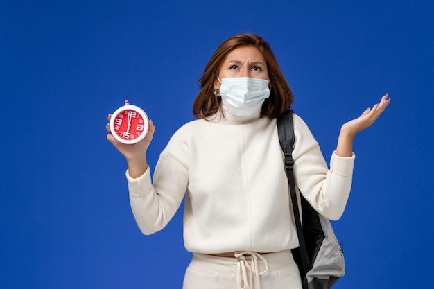 正面図マスクを着用し、青い壁に時計を保持している白いジャージの若い女子学生