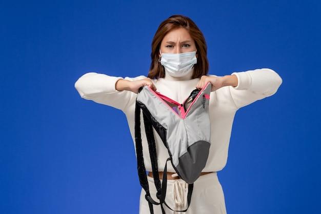 Вид спереди молодая студентка в белом джерси в маске и держит рюкзак на синей стене