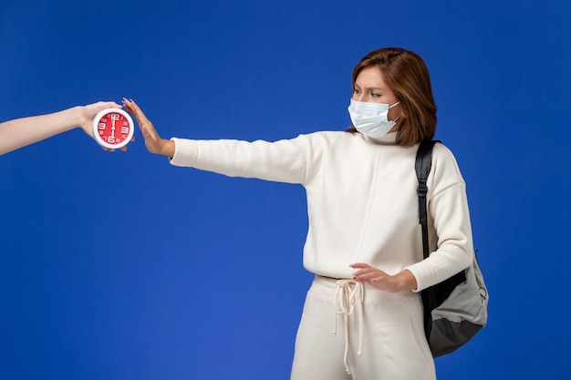青い壁に時計と女性の怖いマスクを身に着けている白いジャージの正面図若い女子学生